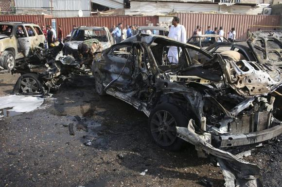People inspect the site of a car bomb attack in Basra, southeast of Baghdad September 30, 2014. The car bomb attack took place in a parking lot and no one was hurt, police sources said. REUTERS/Stringer