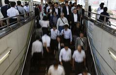 Personas bajan la escalera en una estación de trenes en el distrito financiero de Tokio. Imagen de archivo, 30 septiembre, 2014. China probablemente registre un crecimiento anual de al menos 7 por ciento a lo largo de los próximos cinco años mientras reajusta su economía para impulsar la demanda doméstica, dijo el nuevo economista jefe del Banco de Desarrollo Asiático el jueves. REUTERS/Yuya Shino
