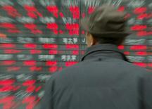 Прохожий изучает котировки на экране у биржи в Токио 1 марта 2004 года. Азиатские фондовые рынки завершили торги вторника разнонаправленно под влиянием местных новостей. REUTERS/Issei Kato