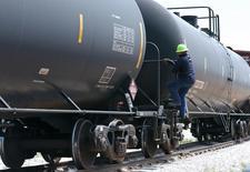 Un trabajador sube a un tren que transporta petróleo en Wyoming. Imagen de archivo, 15 julio, 2014. La gubernamental Administración de Información de Energía de Estados Unidos recortó su previsión para la producción de crudo del país en 2015 a 9,50 millones de barriles por día desde los 9,53 millones de bpd el mes anterior, según un reporte mensual de la agencia.. REUTERS/Rick Wilking