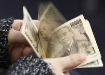 Женщина пересчитывает купюры валюты иена в Токио 28 февраля 2013 года. Курс иены растет, потому что инвесторы не хотят рисковать, узнав о спаде промышленного производства в Германии и снижении прогноза роста мировой экономики МВФ. REUTERS/Shohei Miyano