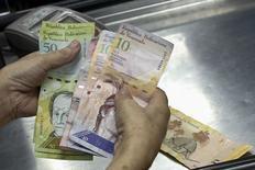Imagen de archivo de un cajero contando bolívares al interior de un supermercado en Caracas, sep 9 2014. Venezuela pagó el miércoles un total de 1.562 millones de dólares tras el vencimiento de un bono soberano más sus respectivos intereses, un desembolso que había mantenido a los mercados en vilo. REUTERS/Carlos Garcia Rawlins