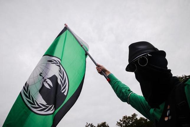 10月10日、アノニマスは中国と香港へのサイバー攻撃を予告した。写真は同集団の旗を手にする人。ベルリンで8月撮影(2014年 ロイター/Thomas Peter)