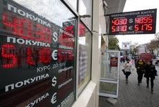 Вывеска пункта обмена валюты в Москве 13 октября 2014 года. Рубль во вторник утром продолжил обновлять минимумы из-за дефицита валюты при ограничении доступа к западным ресурсам и на фоне падения нефтяных цен, при этом ЦБР регулярно сдвигает вверх валютный коридор, что, по оценкам участников рынка, оказывает дополнительное спекулятивное давление на рубль. REUTERS/Sergei Karpukhin