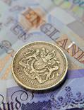 Монета и купюра британского фунта в Лондоне 17 июня 2008 года. Евро и фунт стерлингов снижаются, а доллар растет, после выхода неожиданно слабых экономических показателей Германии и Великобритании. REUTERS/Toby Melville