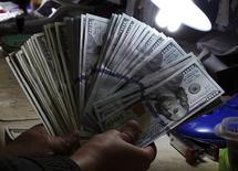 Un empleado cuenta dólares al interior de una casa de cambios en Manila, ene 15 2014. El dólar tocó un mínimo en tres semanas frente al euro y de más de un mes respecto al yen el miércoles, después de que débiles datos económicos de Estados Unidos sobre ventas minoristas y precios al productor aumentaran las preocupaciones de que la Reserva Federal retrase su primera subida de las tasas de interés.          REUTERS/Romeo Ranoco