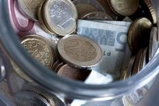 Монеты и банкноты валюты евро в Будапеште 6 января 2012 года. Евро снизился в четверг наряду с такими высокодоходными валютами, как норвежская крона и австралийский доллар, так как распродажа испанских и итальянских гособлигаций усилила растущее чувство паники на финансовых рынках.  REUTERS/Bernadett Szabo