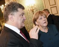 Ukraine's President Petro Poroshenko (L) talks with German Chancellor Angela Merkel during a meeting on the sidelines of a Europe-Asia summit (ASEM) in Milan October 17, 2014.  REUTERS/Daniel Dal Zennaro/Pool   (ITALY  - Tags: POLITICS)