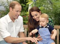 Britain's Catherine, Duchess of Cambridge, carries her son Prince George as he examines a butterfly on the hand of his father Prince William during a visit to the Sensational Butterflies exhibition at the Natural History Museum in London, July 2, 2014. REUTERS/John Stillwell/Pool