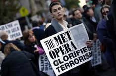 A protester holds a sign during a rally across from Lincoln Center and the New York Metropolitan Opera during a demonstration in New York, October 20, 2014. REUTERS/Mike Segar