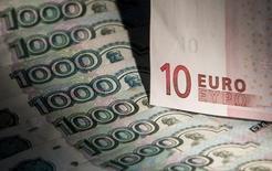 Банкноты российского рубля и евро в Москве 17 февраля 2014 года. Рубль торгуется с незначительными изменениями утром вторника, но при этом сумел обновить абсолютный минимум в паре с евро и протестировать границу валютных интервенций ЦБ. REUTERS/Maxim Shemetov