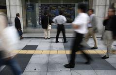 Transeúntes observan una pantalla que muestra índices económicos en Tokio, 20 octubre, 2014. Las bolsas de Asia languidecían el martes tras renunciar a unas pequeñas ganancias, luego de que un alivio modesto por unos datos que mostraron que China creció más que lo esperado fue reemplazado por el temor sobre la pérdida del impulso en la segunda mayor economía del mundo. REUTERS/Yuya Shino