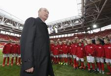 Russian President Vladimir Putin talks to young soccer players during a visit to Spartak's stadium Otkritye Arena in Moscow, August 27, 2014. REUTERS/Sergei Karpukhin