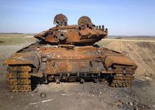 A destroyed T-72 tank, which presumably came from Russia, is seen on a battlefield near separatist-controlled Starobesheve, eastern Ukraine, October 2, 2014. The burnt-out remains of dozens of tanks and armoured vehicles in fields near the small village of Horbatenko bear witness to the ferocity of a battle that turned the tide of the conflict in eastern Ukraine. Among the debris, Reuters found the blackened carcasses of what military experts have since identified as two Russian army tanks, supporting statements by Kiev and the West that the rebels were backed by troops and equipment sent by Moscow. Moscow denies the accusations though the rebels had been on the brink of defeat until late August, when the Ukrainian government says they received an injection of soldiers and weapons from Russia. Picture taken October 2, 2014. To match Exclusive UKRAINE-CRISIS/TANKS REUTERS/Maria Tsvetkova (UKRAINE - Tags: CONFLICT CIVIL UNREST POLITICS MILITARY)