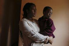 Zuru Pewu holds her four-year-old son Micah inside a home in the Staten Island borough of New York October 23, 2014. Pewu, 29, who emigrated from Liberia in 2005, and her son Micah recently underwent an experience where they were insulted and linked to the spread of the Ebola virus.     REUTERS/Shannon Stapleton