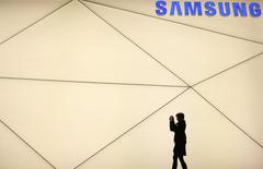 A woman takes a picture outside the Samsung stand at the Mobile World Congress in Barcelona February 24, 2014.   REUTERS/Albert Gea