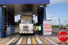 Белорусские пограничники проверяют грузовки на границе с Россией 17 июня 2009 года. Россия может ограничить транзит продовольствия из Белоруссии и с Украины в Казахстан, поскольку подозревает, что этот маршрут используется для поставки на российской рынок западных продуктов, запрещённых Кремлём в ответ на санкции, сообщило в четверг госинформагентство РИА Новости. Астана ответила, что не позволит ограничить ввоз продовольствия из ЕС. REUTERS/Stringer