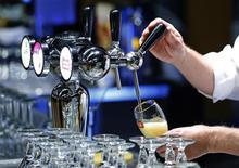 Un mesero sirve un vaso de cerveza del fabricante Anheuser-Busch InBev durante una reunión de sus accionistas en Bruselas. Imagen de archivo, 30 abril, 2014. Anheuser-Busch InBev, el fabricante de cerveza más grande del mundo, reportó un aumento menor que lo esperado de sus ganancias en el tercer trimestre, luego de que los mayoristas en Estados Unidos recortaron inventarios y Brasil se estancó después de la Copa Mundial de fútbol. REUTERS/Yves Herman
