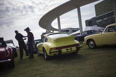 Men stand near a 1974 Porsche 911 Carrera Coupe ahead of an auction for classic vehicles run by the Motostalgia auction house in Austin, Texas October 30, 2014. REUTERS/Adrees Latif