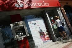 Una mujer abre la puerta de una de las sedes del banco Santander en El Masnou, cerca de Barcelona. Imagen de archivo, 10 septiembre, 2014.  El banco español Santander reportó el martes un aumento de un 32 por ciento en su ganancia neta en los primeros nueve meses del año respecto al mismo período del 2013, superando las previsiones gracias a la mejora de los ingresos, una mayor reducción de costos y unas menores provisiones. REUTERS/Albert Gea