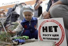 """Ребенок с игрушечными машинками на акции протеста против роста цен на топливо у офиса Роснефти в Ставрополе 10 сентября 2008 года. Ряд депутатов Госдумы предлагают премьеру РФ отказаться от """"налогового маневра"""" в нефтяной отрасли - изменений в налогообложении, которые добывающие компании и ведомства мучительно согласовывали в течение нескольких месяцев. REUTERS/Eduard Korniyenko"""