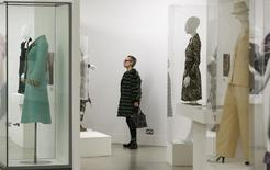 """A visitor looks at clothing on display in the """"Women Fashion Power exhibition at the Design Museum in London November 4, 2014. REUTERS/Suzanne Plunkett"""