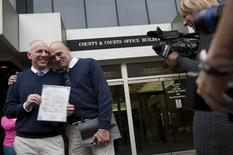 Terrence Hall (L) and Christopher DeCaria (R) display their marriage license to the media outside of the Mecklenburg County Register of Deeds office in Charlotte, North Carolina, October 13, 2014.  REUTERS/Davis Turner
