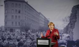 German Chancellor Angela Merkel speaks in front of a photograph showing Bernauer Strasse in November 1989 at the exhibition opening during a ceremony marking the 25th anniversary of the fall of the Berlin Wall at a memorial in Bernauer Strasse in Berlin, November 9, 2014.   REUTERS/Fabrizio Bensch