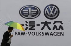 A man holds an umbrella as he walks past a company logo of FAW-Volkswagen at an automobile exhibition in Fuyang, Anhui province, September 12, 2014.  REUTERS/Stringer