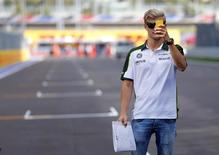 Caterham Formula One driver Marcus Ericsson of Sweden uses his smartphone upon arriving at the Sochi Autodrom circuit October 9 ,2014. REUTERS/Laszlo Balogh