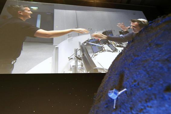 Andrea Accomazzo (R) Spacecraft Operations Manager (SOM) of the European Space Operations Centre (ESOC) seen on a video projection behind a model of the Philae lander, reacts after the successful landing of the Philae lander on comet 67P- Churyumov-Gerasimenko, at the European Space Agency's (ESA) headquarters in Darmstadt November 12, 2014. REUTERS-Ralph Orlowski