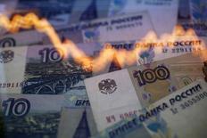 График колебания курса рубля к доллару на фоне рублевых купюр в Варшаве 7 ноября 2014 года. Рубль значительно падал в цене на торгах четверга вслед за снижением нефти к новым многолетним минимумам, подо что и набирались краткосрочные спекулятивные позиции, вечернее закрытие которых немного подняло рублевые котировки с сессионного дна. REUTERS/Kacper Pempel