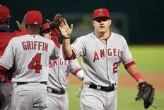 Sep 23, 2014; Oakland, CA, USA; Los Angeles Angels center fielder Mike Trout (27) high fives first base coach Alfredo Griffin (4) after defeating the Oakland Athletics 2-0 at O.co Coliseum. Mandatory Credit: Ed Szczepanski-USA TODAY Sports