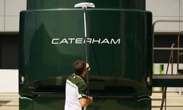 A member of the Caterham Formula One team cleans one of the team vehicles ahead of the British Grand Prix at the Silverstone race circuit, central England, July 3, 2014. REUTERS/Phil Noble/Files
