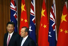 China's President Xi Jinping (L) and Australia's Prime Minister Tony Abbott watch as free trade deals are signed during a signing ceremony at Parliament House in Canberra November 17, 2014. REUTERS/David Gray