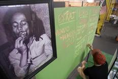 A portrait of reggae legend Bob Marley hangs next to a menu of marijuana products at the medical marijuana farmers market at the California Heritage Market in Los Angeles, California July 11, 2014. REUTERS/David McNew