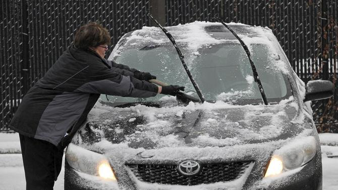 A woman scrapes ice from her car's windshield in the parking lot of a grocery store in Minneapolis, November 10, 2014. REUTERS-Eric Miller