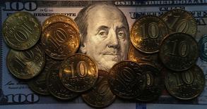 Долларовая купюра и рублевые монеты в Санкт-Петербурге 22 октября 2014 года. Рубль существенно подорожал на пятничных торгах в ожидании расширения продаж экспортной выручки под оставшиеся крупные ноябрьские налоги и на фоне подросшей нефти. REUTERS/Alexander Demianchuk