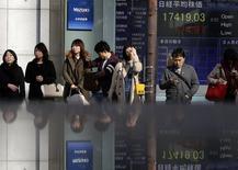Personas frente a una pantalla electrónica que muestra índices económicos en Tokio. Imagen de archivo, 19 noviembre, 2014.  Las bolsas de Asia cedían el martes parte de las ganancias que anotaron esta semana gracias al recorte de las tasas de interés de China, y los precios del petróleo caían mientras los operadores reducen sus expectativas de un recorte significativo de la producción de la OPEP en la reunión que el grupo sostendrá esta semana. REUTERS/Yuya Shino