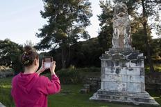 Menina tira foto de estátua de leão de mármore perto de local de escavação arqueológica na cidade de Amphipolis, no norte de Grécia. 22/11/2014 REUTERS/Alexandros Avramidis