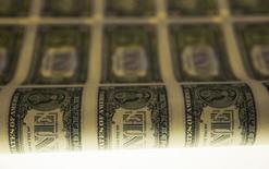 Долларовые купюры во время печати в Бюро гравирования и печати Казначейства США в Вашингтоне 14 ноября 2014 года. Курс доллара снижается к иене после разочаровавшей инвесторов статистики США, вызвавшей также снижение доходности американских облигаций. REUTERS/Gary Cameron