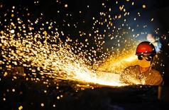 A worker wearing protective glasses welds steel products at a heavy equipment manufacturing factory in Luoyang, Henan province May 1, 2013. REUTERS/China Daily