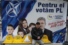 Мужчина у предвыборного щита Либеральной партии в Кишиневе 29 ноября 2014 года. Три проевропейских партии Молдавии получают необходимое для формирования новой коалиции число голосов в результате воскресных парламентских выборов, полагают эксперты. REUTERS/Gleb Garanich