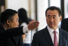 A man shows the way for Wang Jianlin (R), Chairman of Wanda, during a meeting with Tencent Chief Executive Officer Pony Ma and Baidu Inc. Chairman and CEO Robin Li, in Shenzhen, Guangdong province, August 29, 2014. REUTERS/Alex Lee