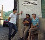 Chef George Mendes (left) strikes up a conversation with two men in Ferreiros do Dao, the home village of Mendes' parents in the central Viseu region, Portugal, July 13, 2013. REUTERS/Genevieve Ko/Handout