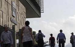 Personas pasan frente a la sede de Petrobras en Rio de Janeiro. Imagen de archivo, 11 abril, 2014.  El regulador de la industria de valores de Brasil, conocido como CVM por sus siglas en portugués, multó el martes por la noche al fondo de pensión que pertenece a trabajadores de la petrolera estatal Petróleo Brasileiro SA por participar en la elección de miembros de la junta y el consejo fiscal, reservada sólo para accionistas minoritarios. REUTERS/Ricardo Moraes