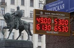 A board showing currency exchange rates, in front of a monument to Prince Yury Dolgoruky who founded Moscow in 1147, in the capital Moscow, December 1, 2014. Oil prices fell to their lowest in five years on Monday, hit by slowing factory activity in China and Europe and hammering emerging market stocks and commodity-linked currencies. Russia's rouble dropped more than 4 percent against the dollar while Malaysia's ringgit, also oil-dependent, was on course for its biggest two-day fall since the 1997-8 Asian financial crisis. REUTERS/Sergei Karpukhin (RUSSIA - Tags: BUSINESS)