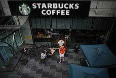 Personas afuera de un local de Starbucks en Shangái. Imagen de archivo, 28 julio, 2014. Starbucks Corp anunció el jueves que añadirá cerveza, vino y refrigerios a miles de tiendas de su cadena de cafeterías, ampliará la oferta de almuerzos y tomará ordenes hechas por teléfono móvil. REUTERS/ Carlos Barria