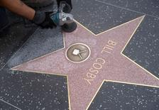 Funcionário limpa estrela de Bill Cosby na Calçada da Fama de Hollywood, em Los Angeles. 05/12/2014.  REUTERS/Phil McCarten