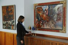 """Embassy intern Leva Andrukaityte poses with the artworks """"Man on a Bull"""" (L) and """"Odalisque of the Grand Canal"""" by artist Theo Tobiasse, at the Embassy of Lithuania in London December 8, 2014. REUTERS/Luke MacGregor"""